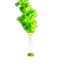 Cubra o redemoinho na água isolada no fundo branco A pintura na água Disseminação macia gotas da tinta verde dentro imagem de stock