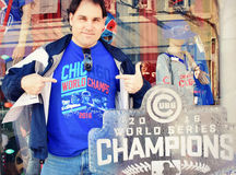 Cubs Fan. A Chicago Cubs fan proudly wears his World Series Champion shirt next to a 2016 Cubs World Champions Ice Sculpture in front of a sporting goods store Stock Images