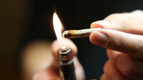 Cucaracha de la junta de la marijuana de la iluminación del hombre metrajes