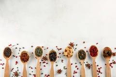 Cucchiai con differenti tipi di tè su fondo leggero immagini stock