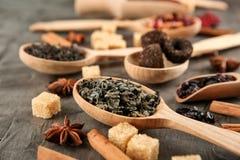 Cucchiai con differenti tipi di tè sulla tavola fotografia stock