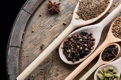 Cucchiai con le varie spezie aromatiche per la cottura sul bordo di legno vecchio, primo piano, disposizione del piano, fuoco sel Fotografia Stock