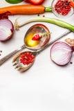 Cucchiai con petrolio e spezie ed ingredienti delle verdure per la cottura sana sul fondo di legno bianco Immagine Stock Libera da Diritti