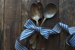 Cucchiai d'annata del metallo, nastro e fondo di legno Fotografie Stock Libere da Diritti