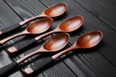 Cucchiai d'annata di legno sui precedenti di legno neri Fotografia Stock
