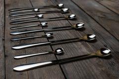 Cucchiai d'argento sistemati sul legno Immagini Stock