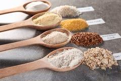 Cucchiai di legno con differenti tipi di farine Immagini Stock