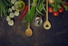 Cucchiai di legno con gli ortaggi freschi ed i condimenti Immagine Stock