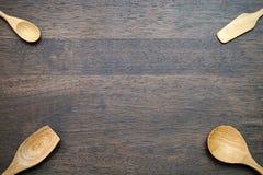 Cucchiai di legno su fondo di legno con lo spazio della copia Fotografie Stock