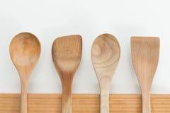 Cucchiai di legno sul tagliere su fondo bianco Immagine Stock Libera da Diritti