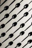 Cucchiai di plastica neri su un fondo grigio Fotografia Stock