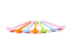 Cucchiai di plastica variopinti del gelato su un fondo bianco Immagini Stock Libere da Diritti