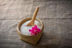 Cucchiai e canestro di legno del riso del gelsomino su di legno Fotografia Stock