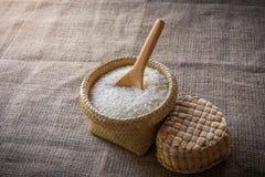 Cucchiai e canestro di legno del riso del gelsomino su di legno Fotografie Stock