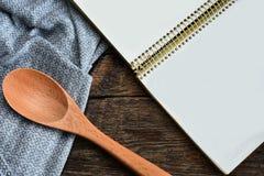 Cucchiai e libro di cucina mescolantesi di legno immagini stock libere da diritti