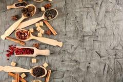 Cucchiai e mestolo con differenti tipi di tè sulla tavola immagini stock