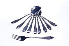 Cucchiai ed una forchetta su una priorità bassa bianca Immagini Stock