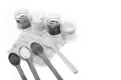Cucchiaiate e barattoli delle spezie isolate su fondo bianco Cucchiai e contenitori di legno con paprica, sale e sale marino Fotografia Stock Libera da Diritti