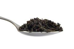Cucchiaino da tè con la foglia di tè nera, isolata Immagini Stock