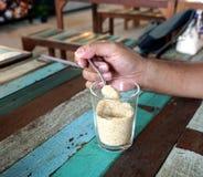 Cucchiaino della tenuta della mano con zucchero Immagine Stock
