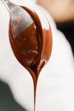 Cucchiaio con cioccolato liquido Immagine Stock