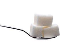 Cucchiaio con i cubi dello zucchero isolati Fotografia Stock