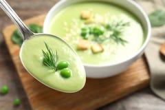 Cucchiaio con la minestra della disintossicazione di verdura fresca fatta dei piselli su fondo vago fotografie stock