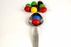 Cucchiaio con le caramelle variopinte Fotografia Stock