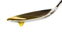 Cucchiaio con olio d'oliva vergine extra e goccia isolati su fondo bianco Fotografia Stock