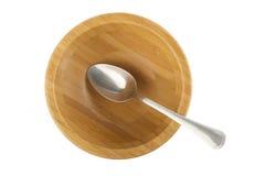 Cucchiaio d'acciaio in ciotola di legno isolata su bianco fotografia stock