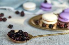 Cucchiaio d'annata con le more fresche nella priorità alta Sui macarons grigi vaghi di un fondo e sulle more fresche Fine in su Fotografia Stock