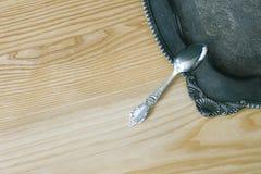 Cucchiaio d'argento sul vassoio d'annata floreale su superficie di legno Fotografia Stock Libera da Diritti