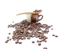 Cucchiaio dei chicchi di caffè su una tazza isolata (messa a fuoco selettiva al cucchiaio) Immagini Stock