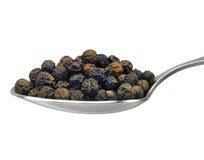Cucchiaio dei grani del pepe nero, isolato sul primo piano bianco e macro Fotografia Stock