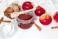 Cucchiaio del miele, barattolo di miele, mele e cannella su un fondo di legno in uno stile rustico fotografia stock libera da diritti
