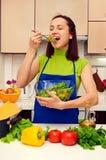Cucchiaio dell'assaggio della donna di insalata fresca nella cucina Fotografia Stock