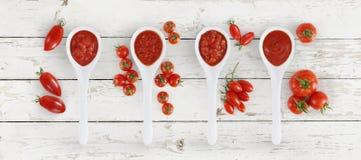 Cucchiaio della salsa al pomodoro con i pomodori e basilico isolato su wh di legno fotografie stock