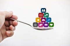 Cucchiaio della tenuta della mano con le icone dell'applicazione di media Media sociali e concetto dipendente di applicazione mob immagini stock libere da diritti