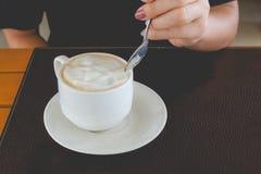 Cucchiaio di caffè della tenuta della mano della donna e caffè caldo di stirring in tazza bianca sulla tavola di legno al caffè fotografia stock