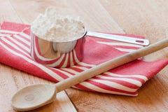 Cucchiaio di cottura e tazza di misurazione Fotografia Stock