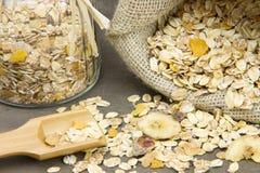 Cucchiaio di legno con i muesli e sacco e barattolo della tela da imballaggio sul backgrou Fotografie Stock