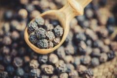 Cucchiaio di legno con i peperoni neri Fotografia Stock Libera da Diritti