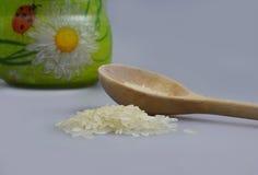 Cucchiaio di legno con il mucchio di riso e di un barattolo Fotografia Stock Libera da Diritti