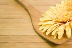 Cucchiaio di legno con un fiore giallo Fotografia Stock