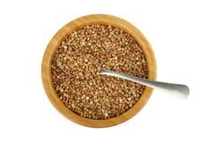 Cucchiaio di legno dell'acciaio e della ciotola con grano saraceno immagini stock