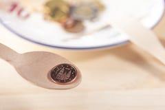 Cucchiaio di legno di eco con una moneta 2 centesimi sopra un piatto bianco con la forcella di eco e dei soldi immagini stock
