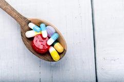 Cucchiaio di legno pieno delle compresse Fondo della farmacia su una tavola bianca Compresse su un fondo bianco Pillole Medicina  Immagine Stock Libera da Diritti