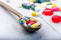 Cucchiaio di legno pieno delle compresse Fondo della farmacia su una tavola bianca Compresse su un fondo bianco Pillole Medicina  Immagini Stock Libere da Diritti