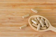 Cucchiaio di legno in pieno di medicina di erbe in chiare capsule, FO ideali Immagini Stock