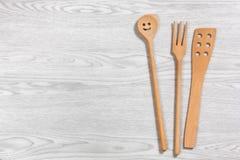 Cucchiaio di legno sorridente ed altri due utensili sull'sedere di legno bianche Fotografia Stock